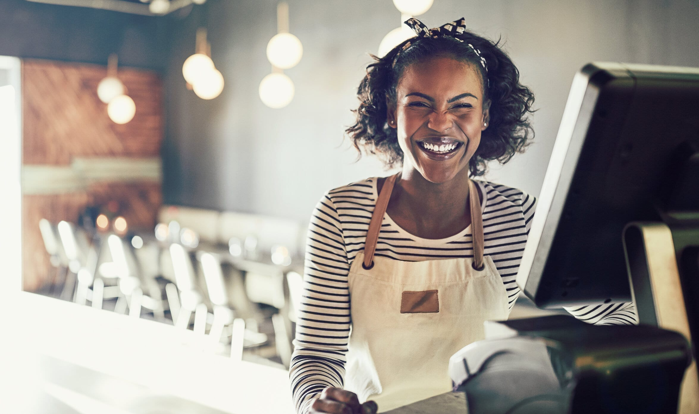 Laughing young African waitress working in a trendy restaurant